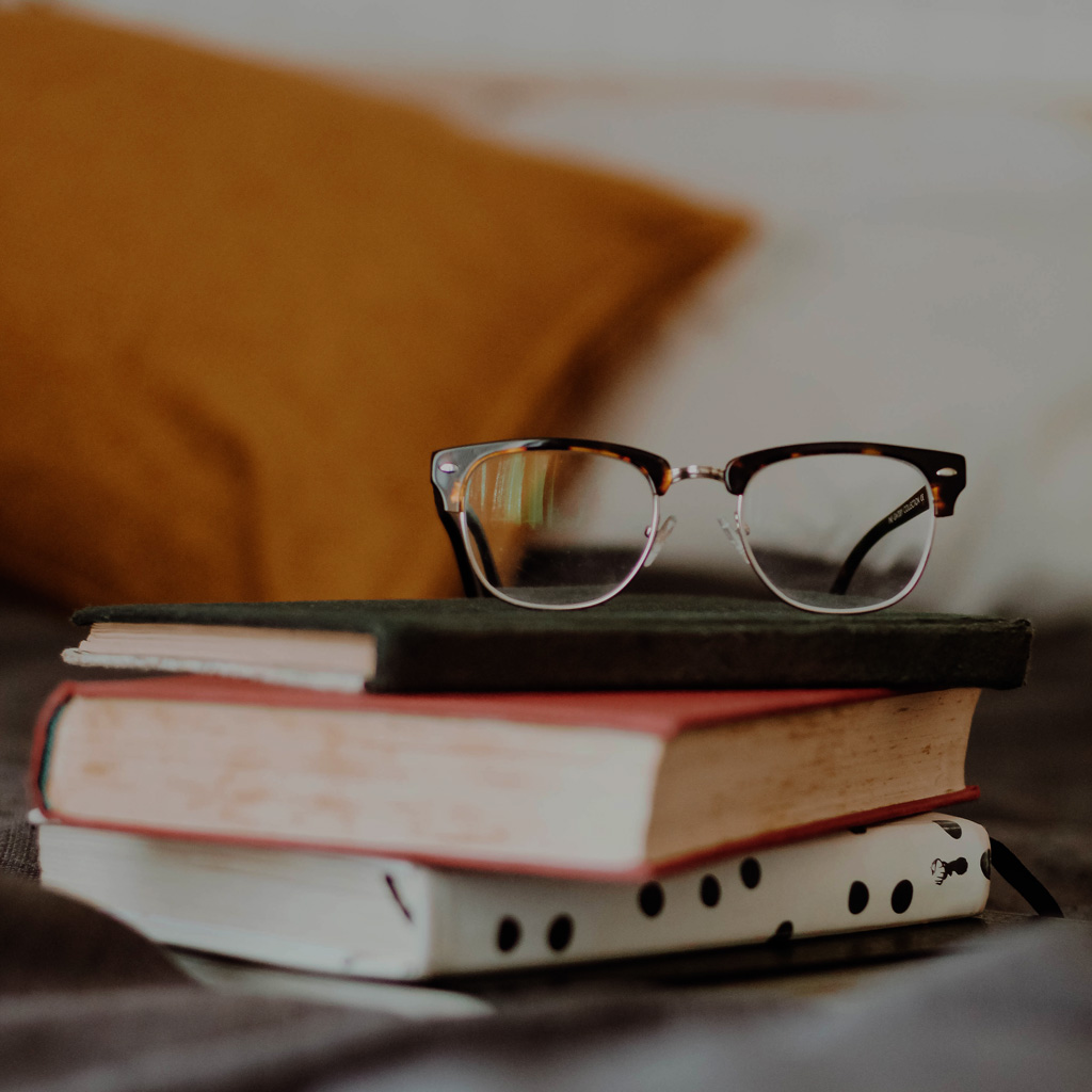 A pile of books with a pair of glasses on top