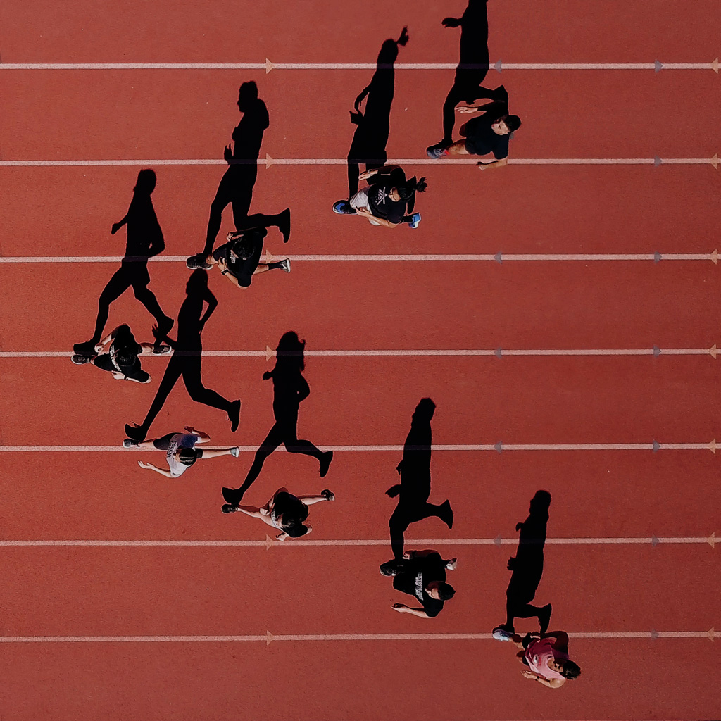An aerial image of a group of people running in formation on a running track. One person is clearly in the lead position