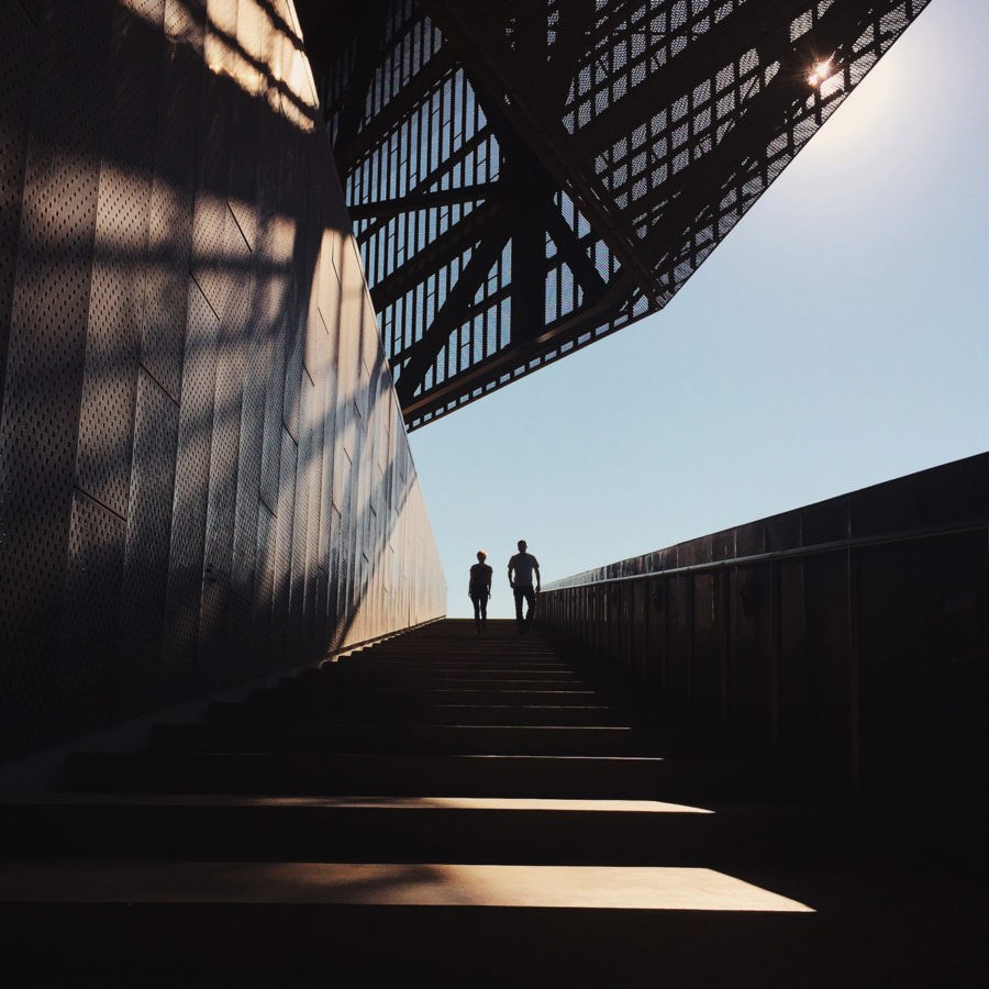 Two people walking up a set of wide and long stairs